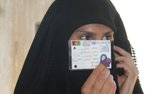 iraqi woman holds her voter registration card