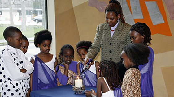 Rwandan women and children light a memorial candle