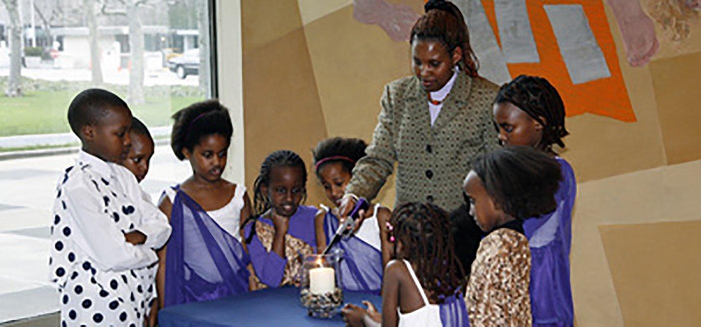 Rwandan women and children light a memorial candle